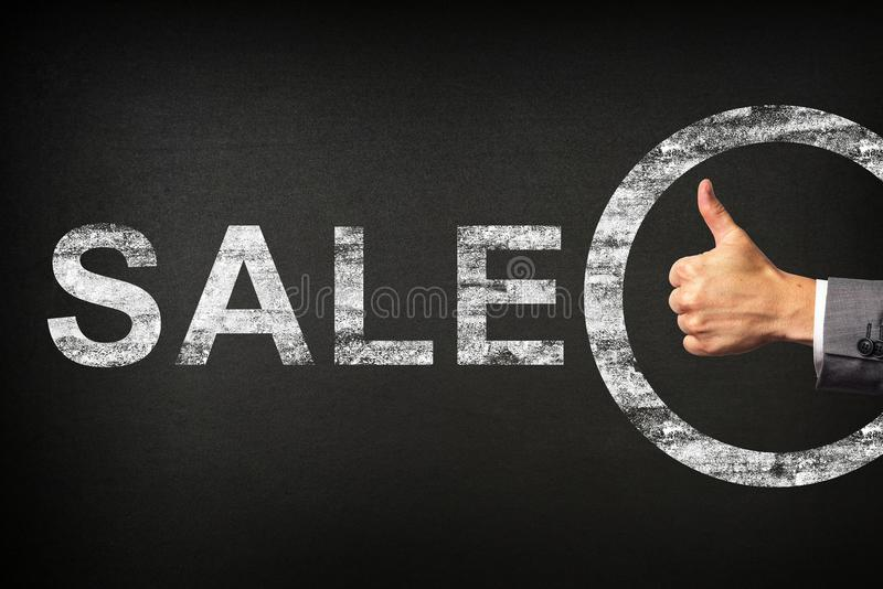显示词组销售的商人的手赞许写在黑板 库存图片