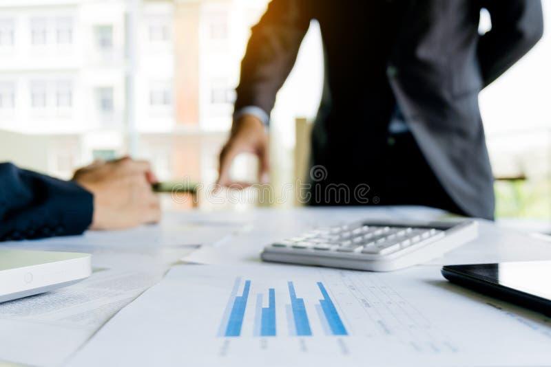 显示财务数据,两个商人的关闭射击片剂站立在背景中 免版税库存图片