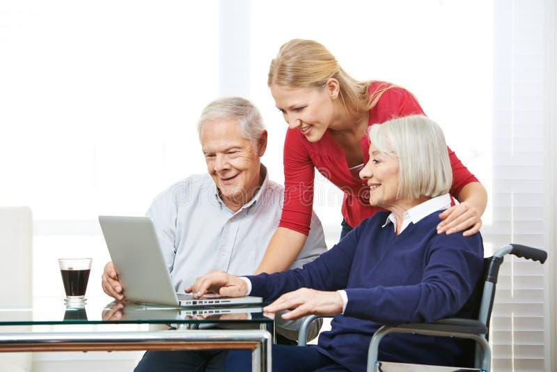 显示资深人计算机用途的孙女 免版税库存照片