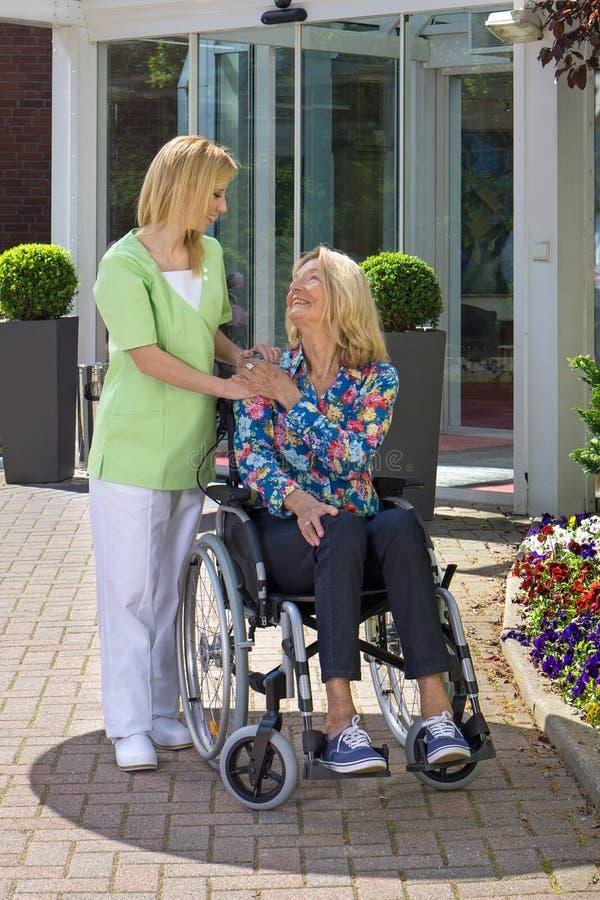 显示资深妇女的护士关心在轮椅 免版税库存照片