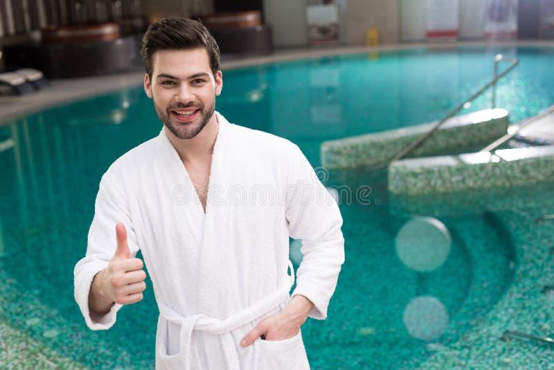 显示赞许和微笑对照相机的浴巾的英俊的年轻人 库存图片