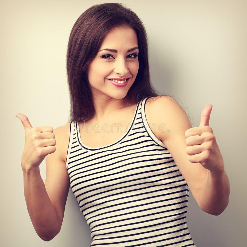 显示赞许标志的愉快的成功的年轻偶然妇女 库存图片