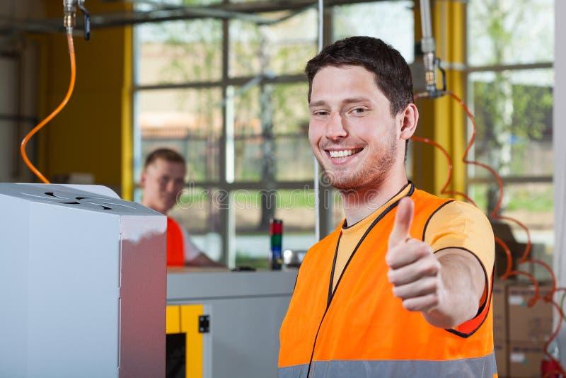 显示赞许标志的机器操作员 免版税库存照片