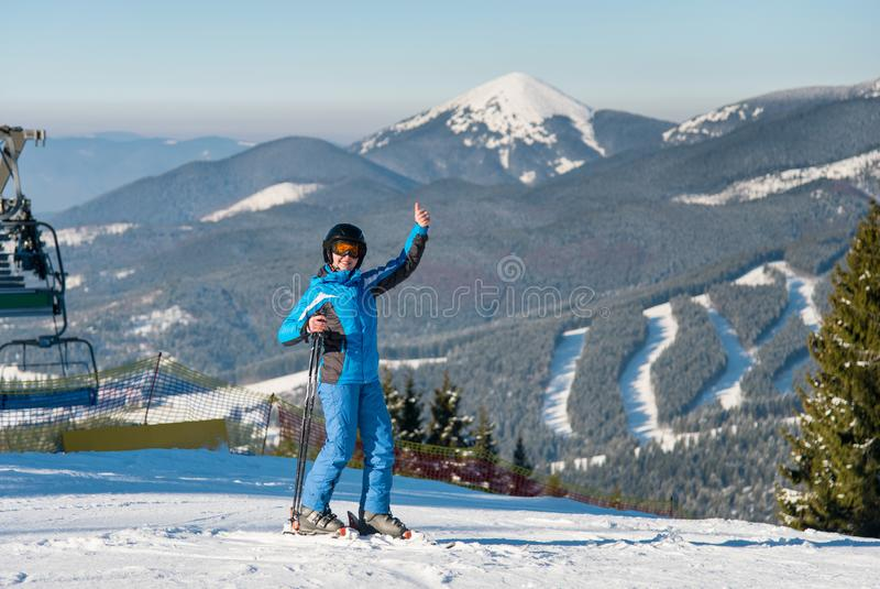 显示赞许的一个微笑的女性滑雪者的全长射击,当滑雪在多雪的倾斜在冬天滑雪胜地时 免版税图库摄影