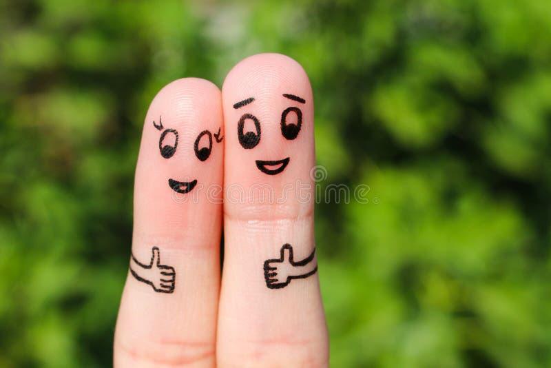 显示赞许的一对愉快的夫妇的手指艺术 库存照片