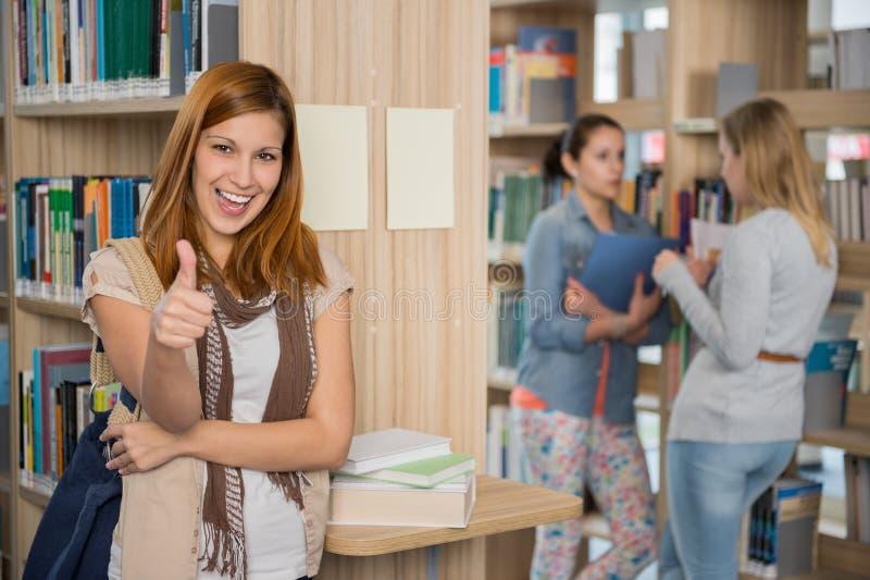显示赞许的学生在图书馆 免版税库存照片