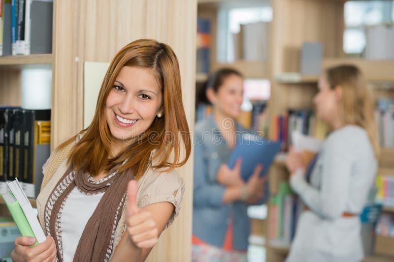 显示赞许的学生在图书馆 免版税库存图片