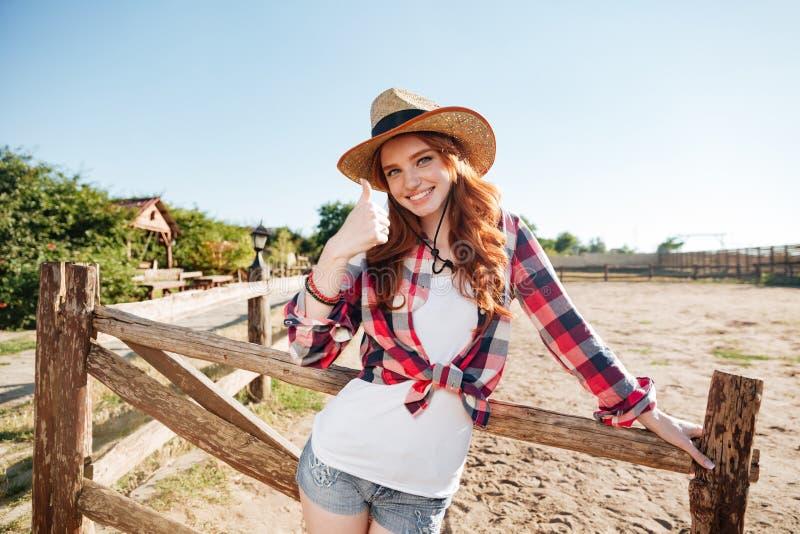 显示赞许的帽子的微笑的快乐的红头发人女牛仔打手势 免版税库存照片