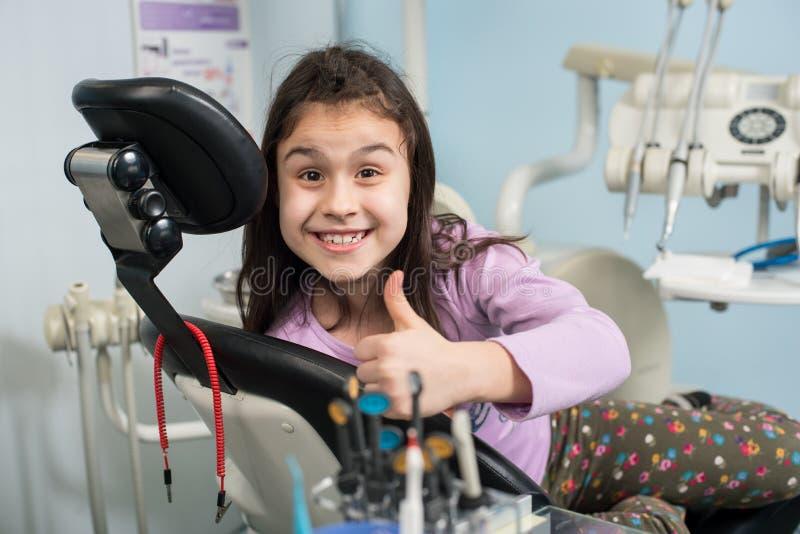显示赞许的快乐的耐心女孩在牙齿诊所办公室 医学、口腔医学和医疗保健概念 免版税图库摄影