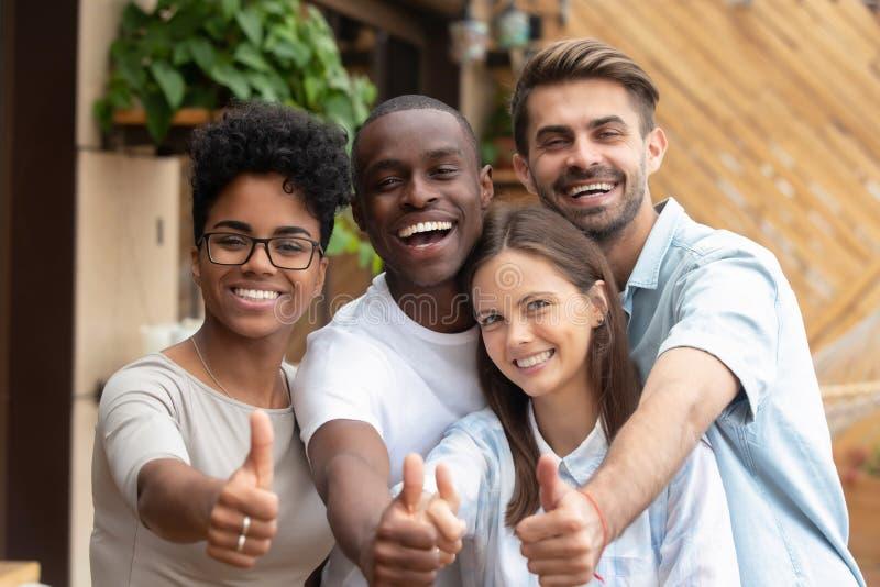 显示赞许的愉快的不同种族的朋友小组看照相机 库存照片