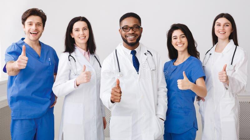 显示赞许的愉快的医疗队,站立在行 免版税库存照片