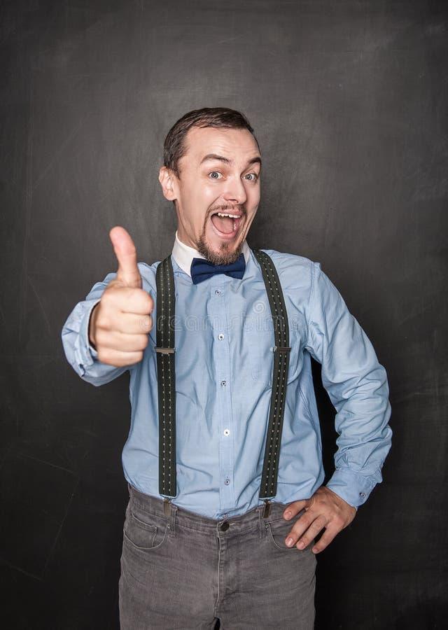 显示赞许的愉快的商人或老师 免版税库存图片