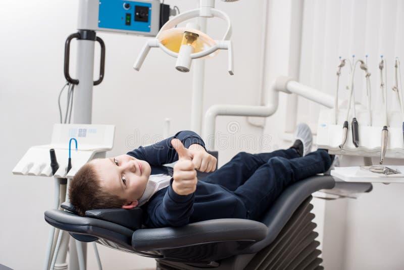 显示赞许的愉快的耐心男孩在牙齿办公室 医学、口腔医学和医疗保健概念 库存图片