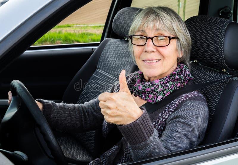显示赞许的汽车的资深妇女 免版税图库摄影