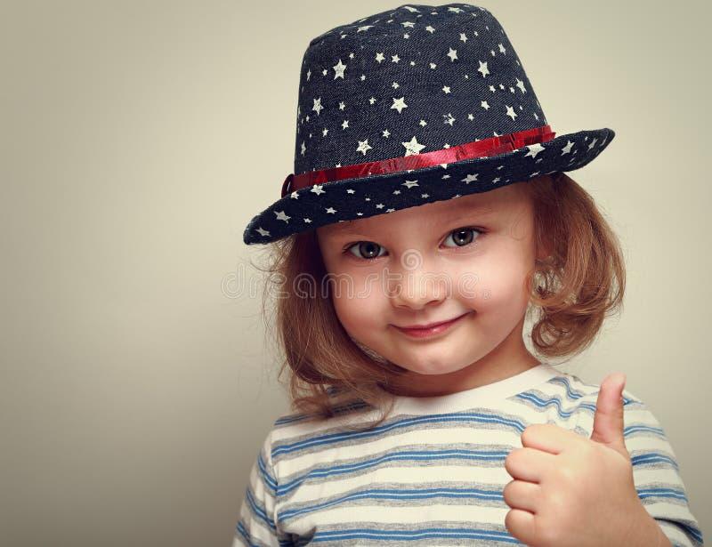 显示赞许的蓝色帽子的微笑的孩子女孩 免版税库存图片
