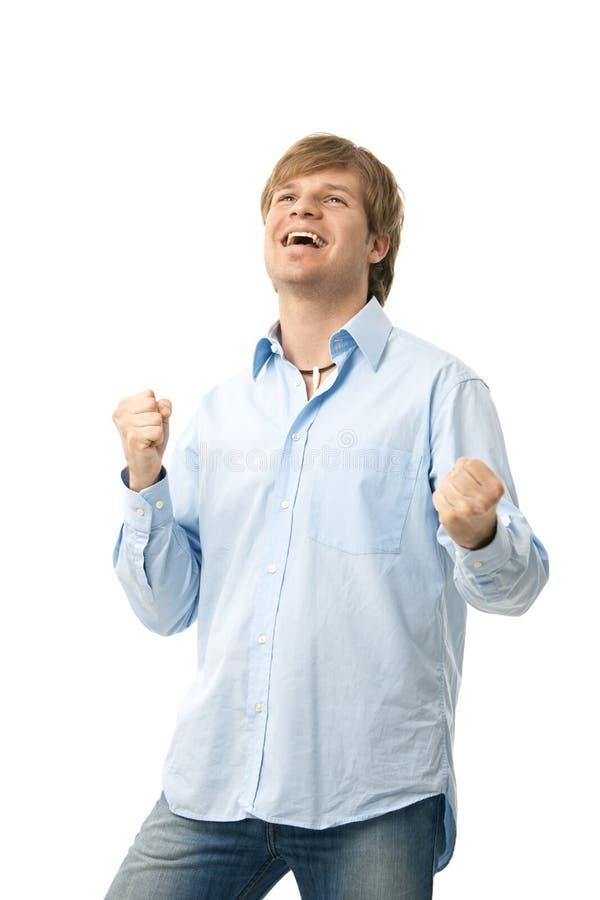 显示赢取的姿态的愉快的年轻人 免版税图库摄影