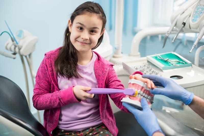 显示适当牙掠过的牙医椅子的女孩使用牙齿下颌模型和大牙刷在牙齿办公室 免版税库存照片