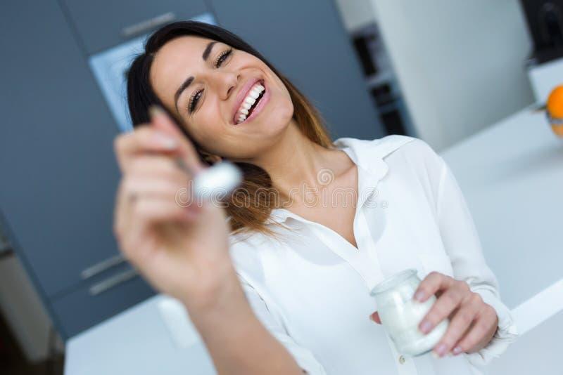 显示酸奶的俏丽的年轻女人对照相机,当在家时吃在厨房 免版税图库摄影