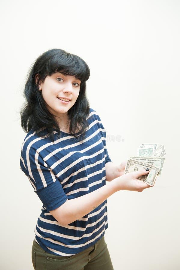 显示金钱的微笑的深色的女孩在手 库存图片