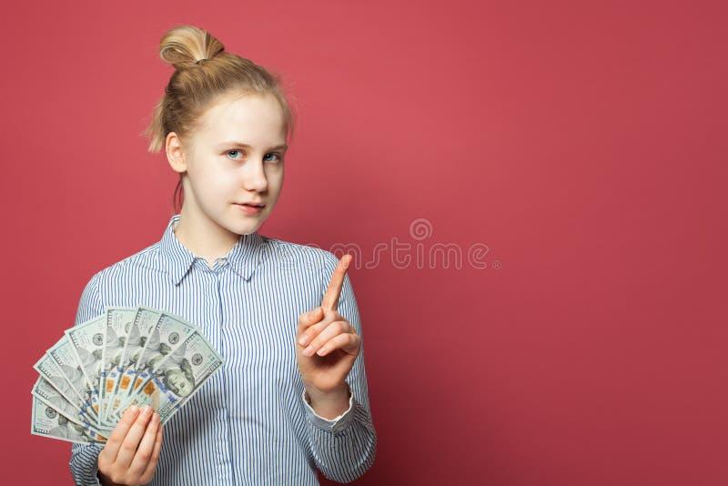 显示金钱美元和指向手指在桃红色背景的聪明的愉快的狡猾少女 库存图片