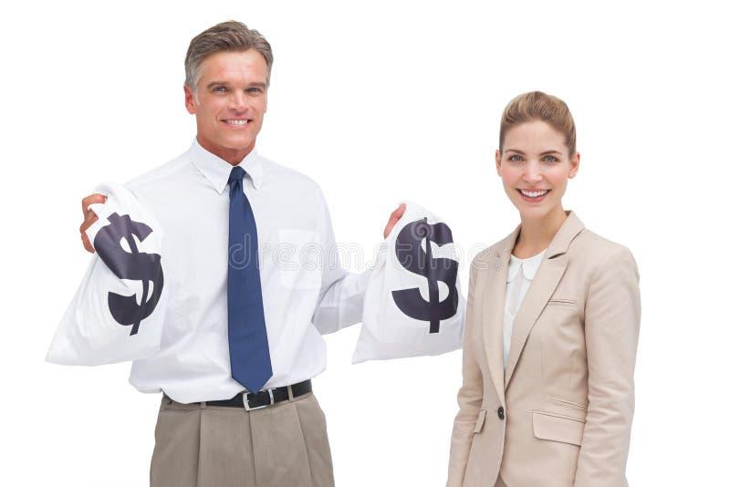 显示金钱袋子的微笑的成熟商人和工友 库存图片