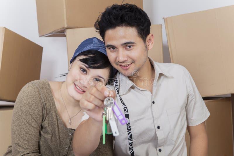 显示钥匙的年轻夫妇对他们新的家 免版税图库摄影