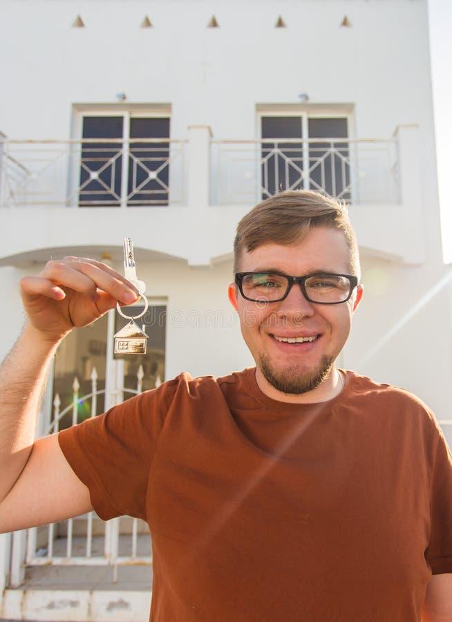 显示钥匙的年轻微笑的人对新的家 房地产、公寓和人概念 免版税库存照片