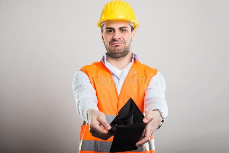 显示钱包的年轻建筑师画象看起来失望 库存图片
