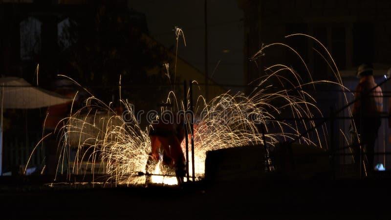 显示铁路夜班工人的夜景围拢由火花 免版税库存图片