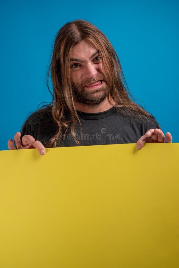 显示鬼脸的恼怒的男性画象,当拿着一副黄色横幅为时做广告 免版税库存图片