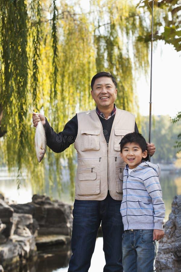 显示鱼捕获的父亲和儿子在湖 库存照片
