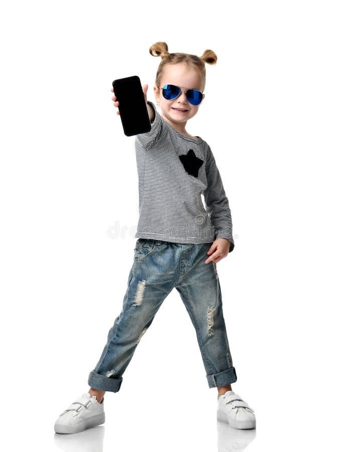 显示黑屏手机的一个微笑的小俏丽的女孩的画象在蓝色太阳镜 免版税图库摄影