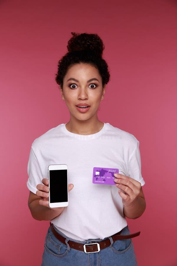 显示黑屏手机的一名激动的年轻非洲妇女的画象被隔绝在桃红色 免版税图库摄影