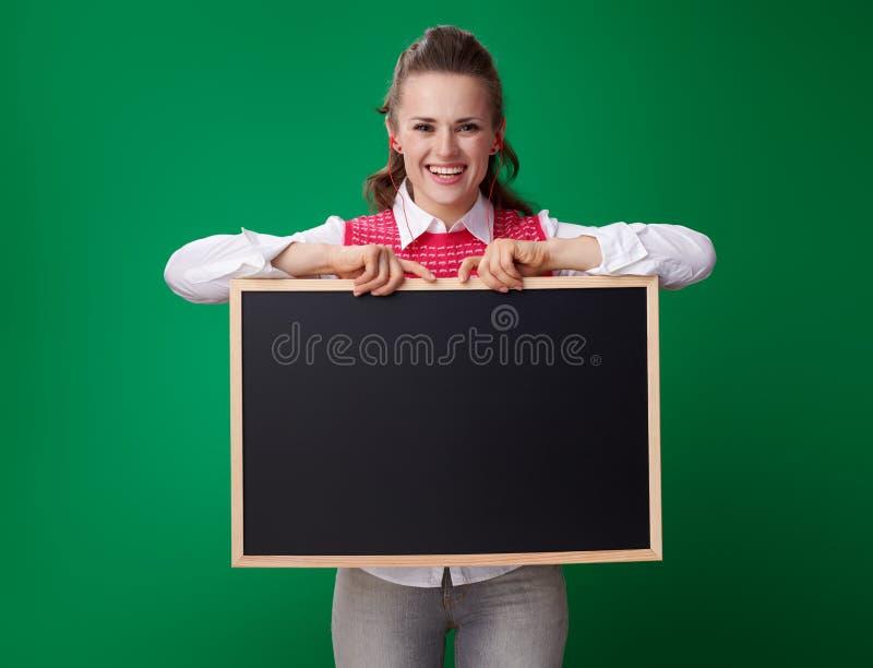 显示黑板的耳机的愉快的现代学生妇女 免版税图库摄影
