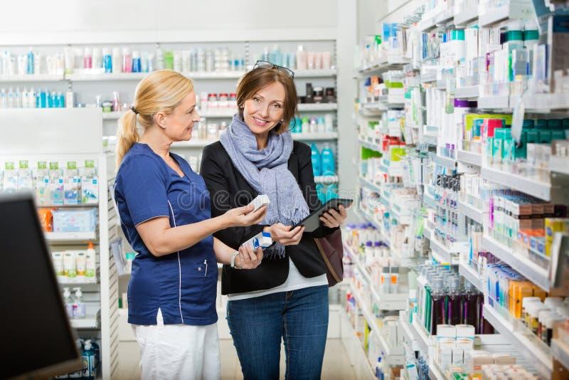 显示医学的顾客支持的药剂师在药房 免版税库存照片