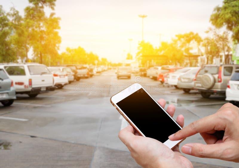 显示黑屏的巧妙的电话在有迷离停车场的人手 库存照片