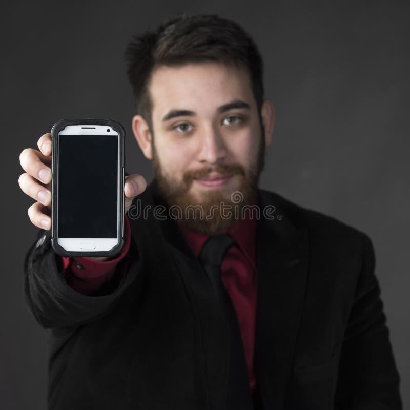 显示他巧妙的电话的年轻商人 库存图片