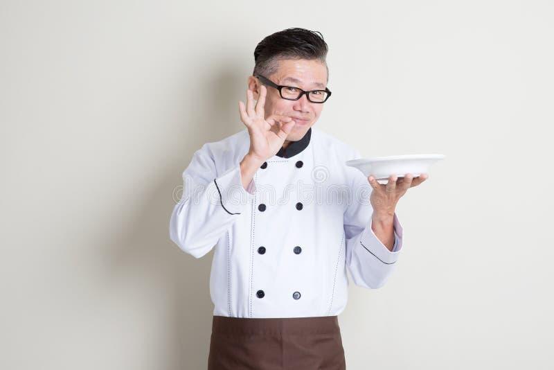 显示满意的手标志的成熟亚裔中国厨师 库存图片