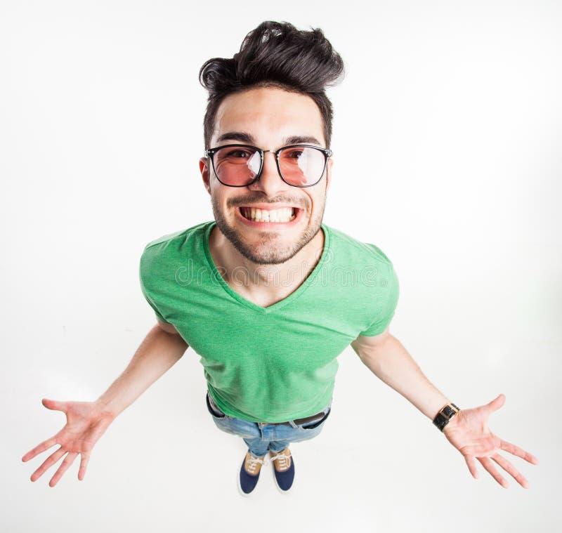 戴显示他棕榈和微笑的行家眼镜的滑稽的英俊的人大-广角射击 免版税库存照片