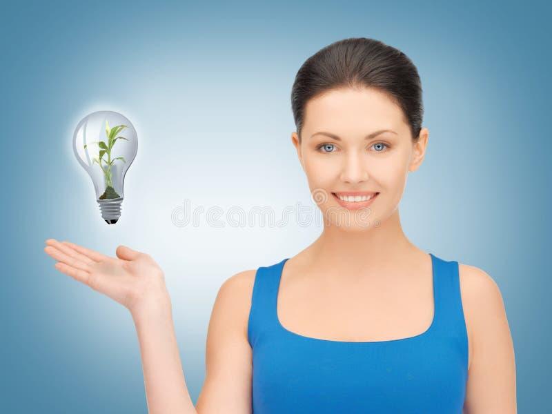 显示绿灯电灯泡的妇女 免版税库存照片