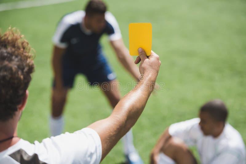 显示黄牌的足球裁判员对球员在比赛期间 免版税库存照片
