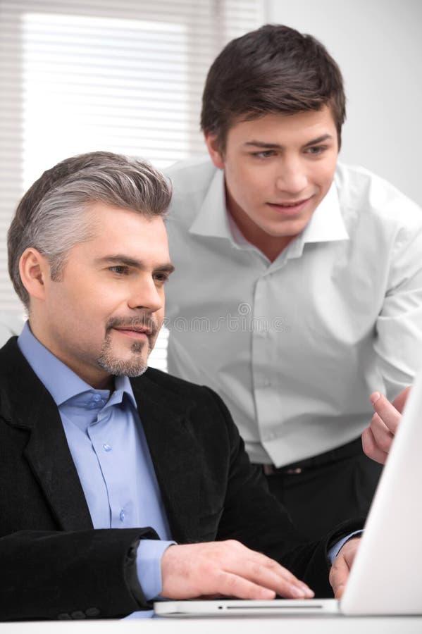 显示他的上司某事在膝上型计算机的年轻商人。 免版税库存照片