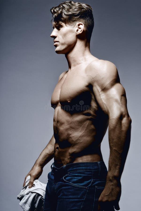 显示他的后面和二头肌肌肉的爱好健美者 库存图片
