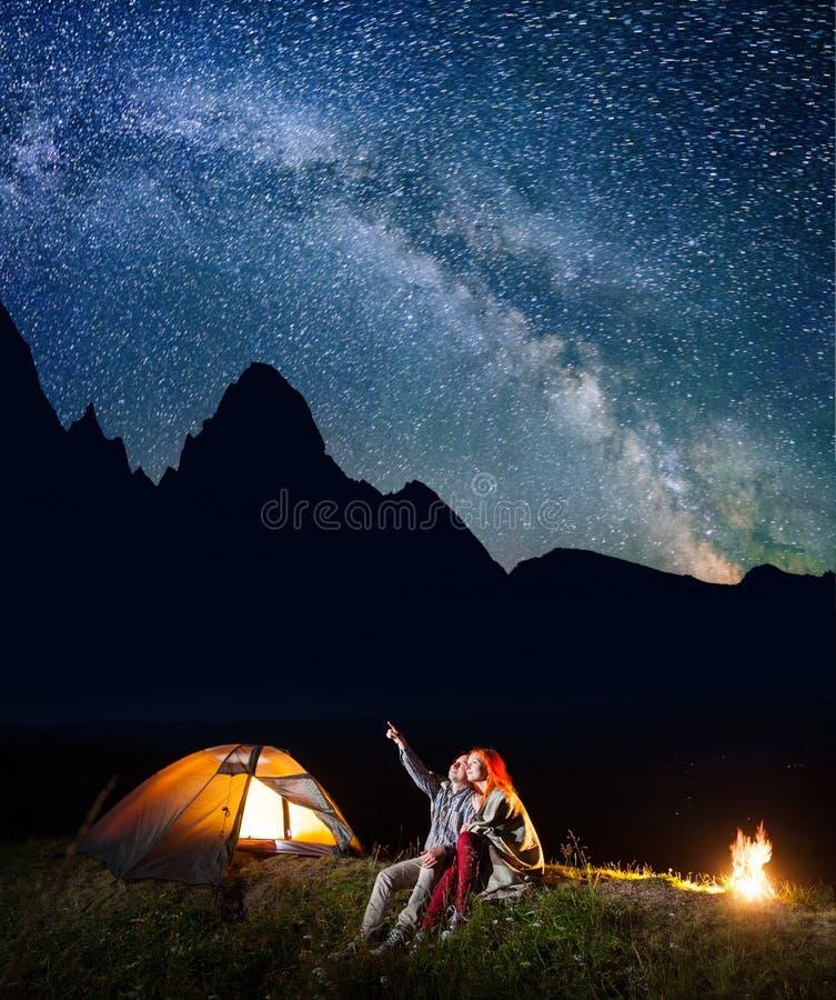显示他的夫人星和银河的远足者人在夜空 在照明设备帐篷和营火附近结合坐 免版税库存照片