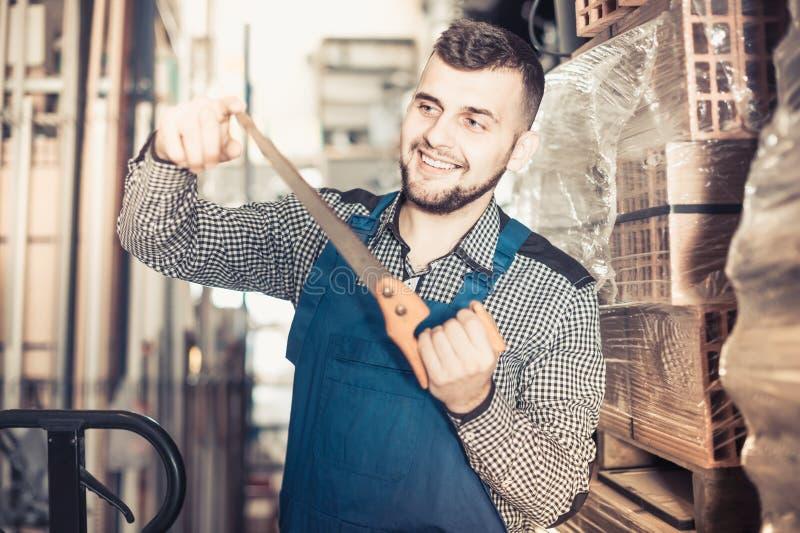显示他的工具的英俊的男性工作者 免版税库存照片