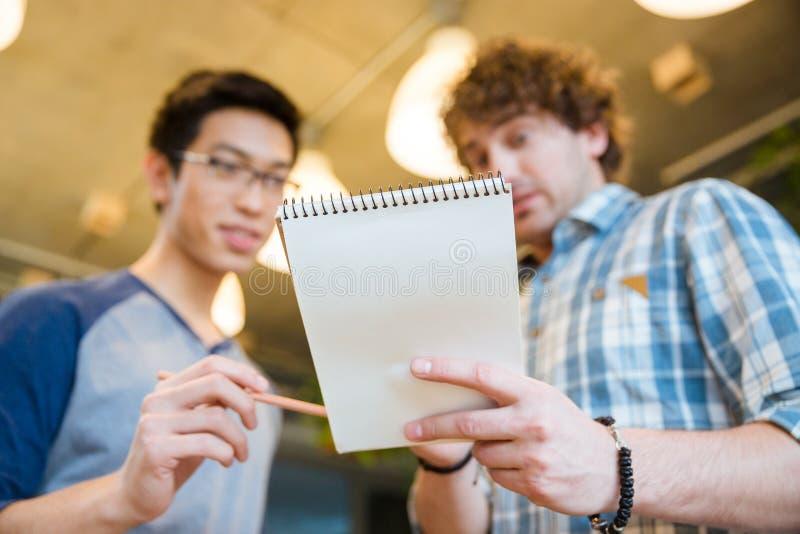 显示他的笔记的学生对朋友 图库摄影