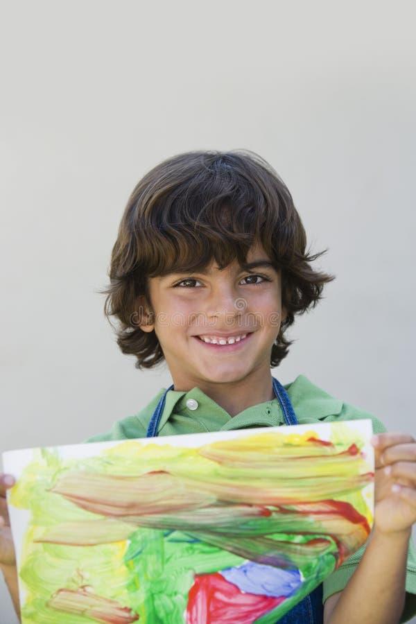 显示他的绘画的愉快的男孩 免版税图库摄影