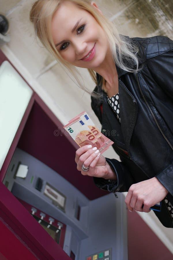 显示从ATM的妇女被撤出的金钱 免版税库存照片