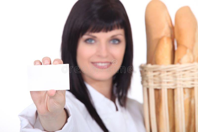 显示businesscard的女性面包师 图库摄影