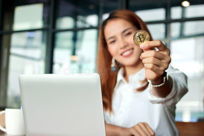 显示cryptocurrency金黄bitcoin硬币的亚裔女商人的手在办公室 在数字式真正金钱 免版税图库摄影